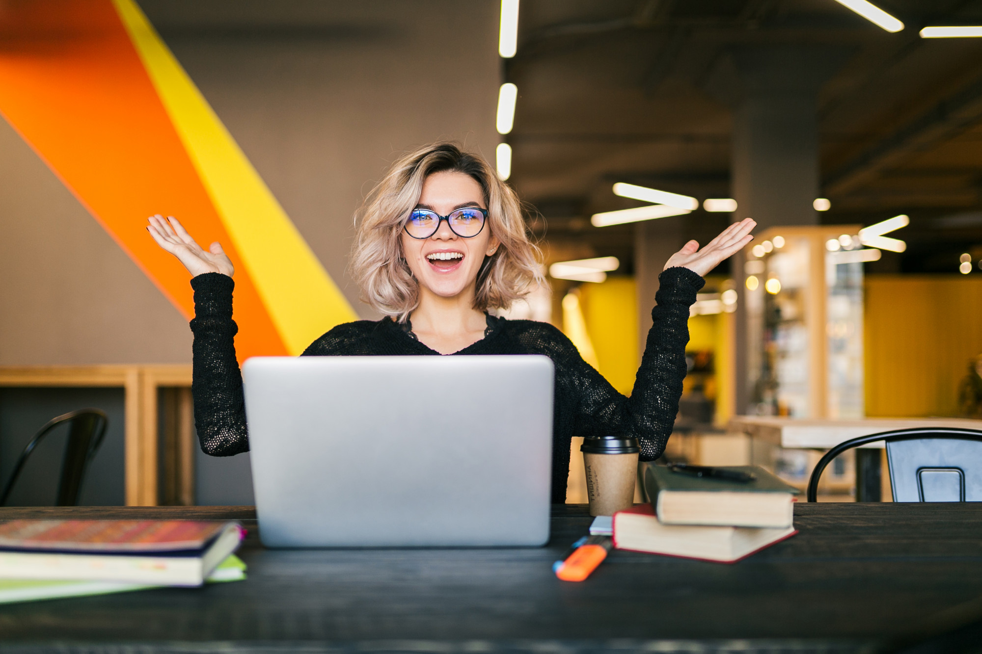funny-happy-excited-young-pretty-woman-sitting-table-black-shirt-working-laptop-co-working-office-wearing-glasses
